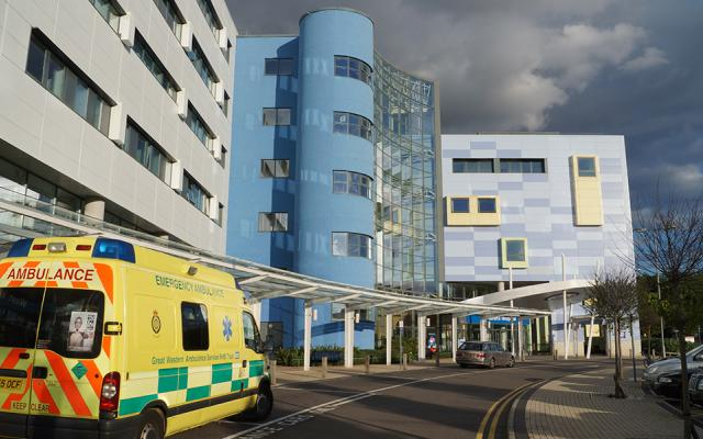 Ambulance parked in front of the John Radcliffe Infirmary, the blue Children's Hospital building in the background