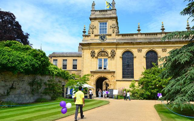 A student holding a balloon walks towards the entrance to Christ College Oxford, bedecked with open day banners