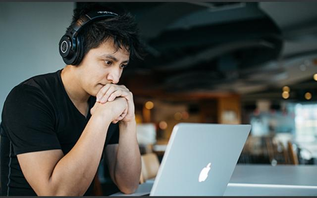 A young man with headphones reading on his laptop in a cafe