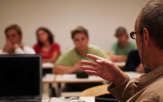 A male lecturer with laptop in the foreground, students in the background