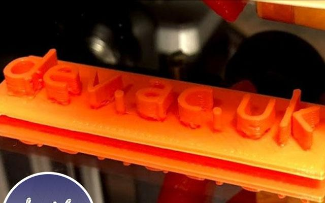 A 3D printout of the letters dev.ac.uk in orange
