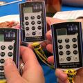 Three students with clickers in their hands wait to vote on the next question