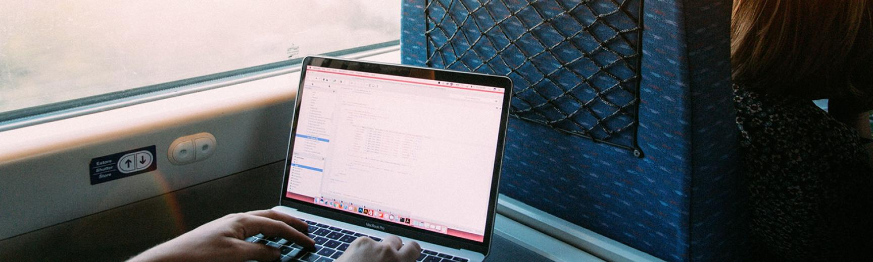 A student working on a laptop on the train