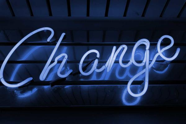 A blue neon light sign saying change