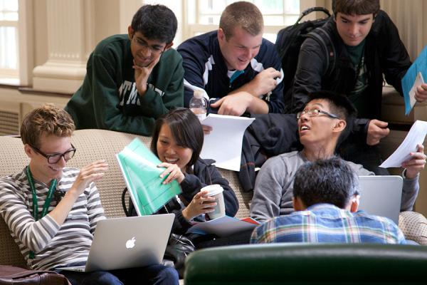 Group of students gather round sofas, one working on a laptop