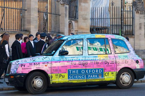 A taxi in colourful livery of the periodic table drives in front of students walking in subfusc in next to the Sheldonian Theatre