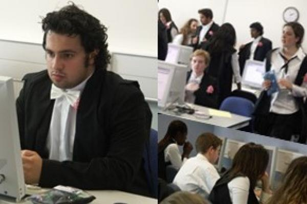Oxford students in subfusc robes wih carnations take exams online in a shared computer room