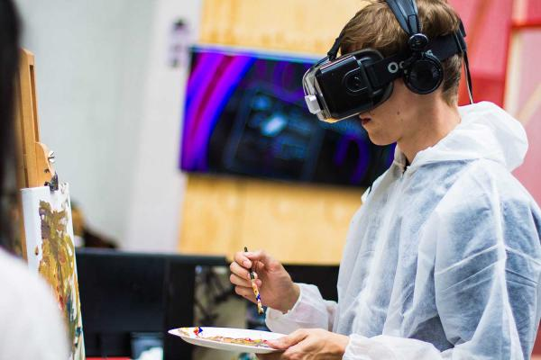 a boy painting while wearing a VR headset