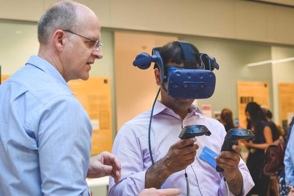 A man helping a student to use a Virtual Reality (VR) headset