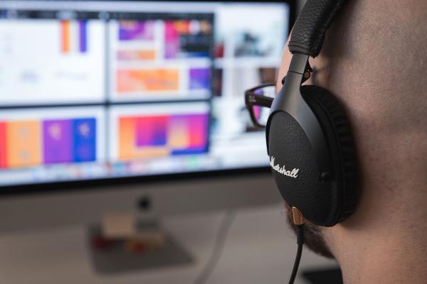 a man wearing big headphones looking at a computer monitor