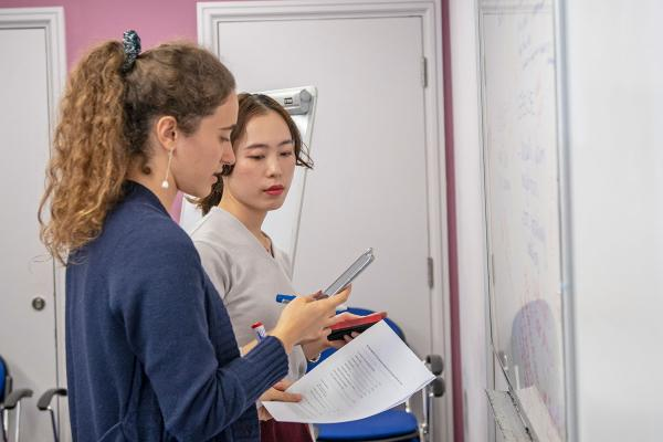 Two female students working on a mobile phone in front of a white board