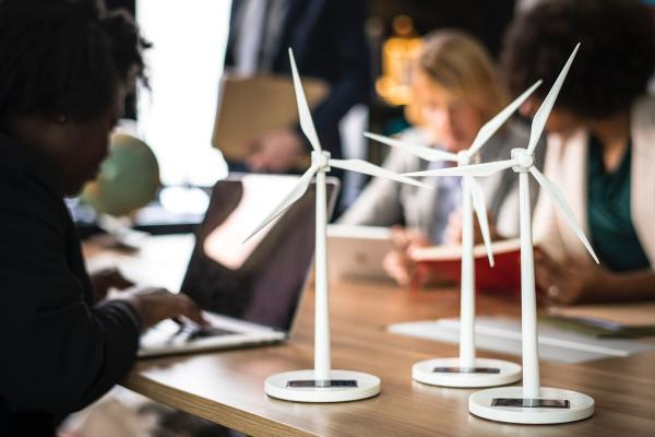 Three women working on laptop and tablet with models of wind turbines on the table
