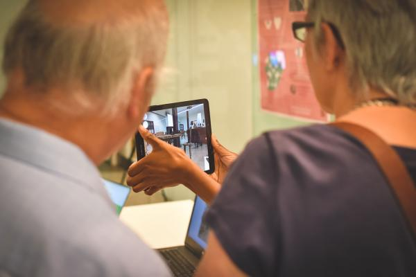 two elderly people looking at an augmented reality (AR) application on a tablet, explained by another woman