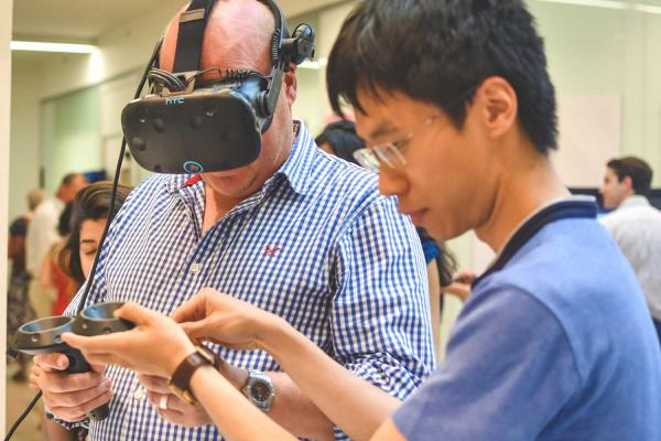 a man trying a Virtual Reality headset with the help of a student