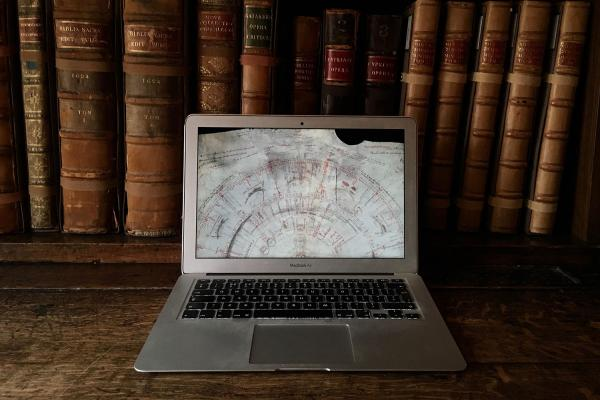 A laptop showing a digitised map in front of old books