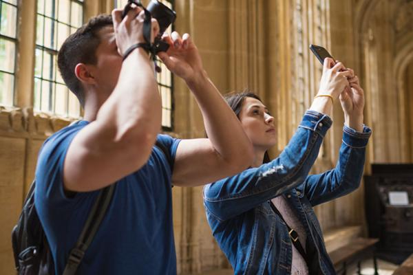 Two students taking photos on their phone and camera inside the Divinity School (Bodleian Library)