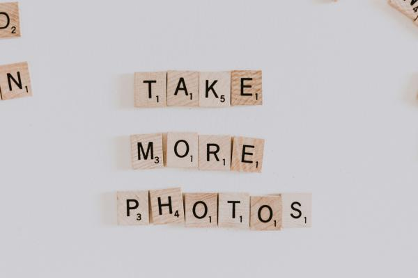 'Take more photos' written with scrabble stones
