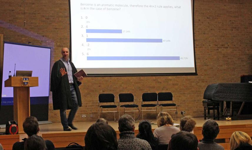 a professor speaking in front of an audience while showing Meetoo polling results on his PowerPoint