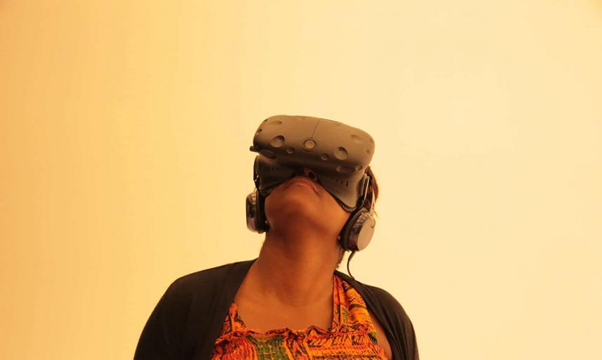 a young woman wearing AR/VR goggles and looking up