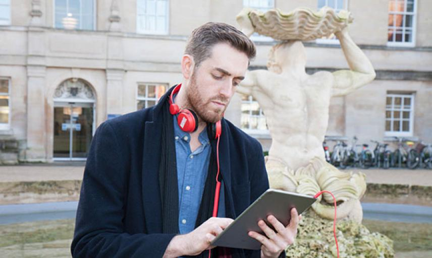 A male student watches a lecture on his tablet in front of the Humanities building