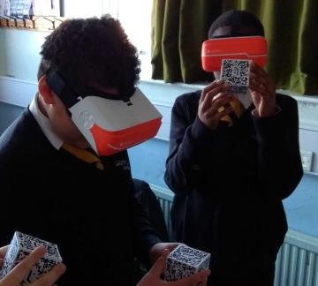 Two pupils wearing VR headsets and handling virtual objects using QR cubes