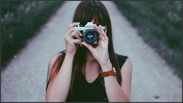 a girl taking a photo with an analogue camera facing the viewer