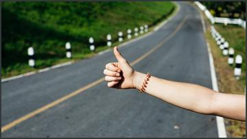 a person hitchhiking holding out hand with thumbs up in front of a road