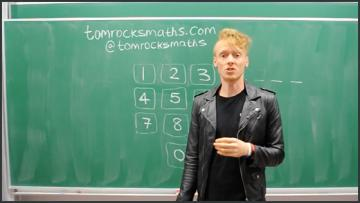 a man talking in front of a blackboard with maths equations