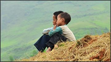 two young boys sitting on a stack of hay looking into distance