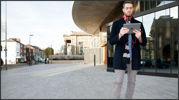 A male student looks at a tablet computer outside the Blavatnik building, Oxford