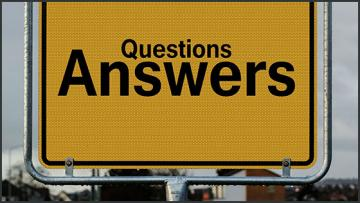A yellow street sign saying questions in small and answers in big typography