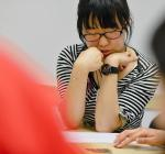 A maths student sits at a table with colleagues working on a problem with coins